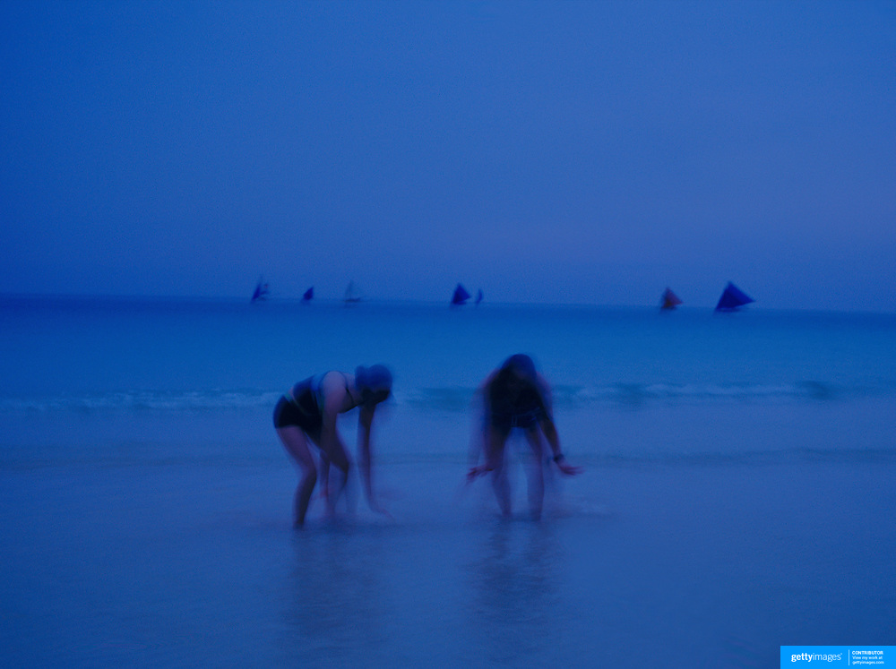 Asian tourists collect shells at dusk in the ocean at White Beach,  Boracay Island, the Philippines on October 6, 2008, Photo Tim Clayton....Asian tourists at White Beach, Boracay Island, the Philippines...The 4 km stretch of White beach on Boracay Island, the Philippines has been honoured as the best leisure destination in Asia beating popular destinations such as Bali in Indonesia and Sanya in China in a recent survey conducted by an International Travel Magazine with 2.2 million viewers taking part in the online poll...Last year, close to 600,000 visitors visited Boracay with South Korea providing 128,909 visitors followed by Japan, 35,294, USA, 13,362 and China 12,720...A popular destination for South Korean divers and honeymooners, Boracay is now attracting crowds of tourists from mainland China who are arriving in ever increasing numbers. In Asia, China has already overtaken Japan to become the largest source of outland travelers...Boracay's main attraction is 4 km of pristine powder fine white sand and the crystal clear azure water making it a popular destination for Scuba diving with nearly 20 dive centers along White beach. The stretch of shady palm trees separate the beach from the line of hotels, restaurants, bars and cafes. It's pulsating nightlife with the friendly locals make it increasingly popular with the asian tourists...The Boracay sailing boats provide endless tourist entertainment, particularly during the amazing sunsets when the silhouetted sails provide picture postcard scenes along the shoreline...Boracay Island is situated an hours flight from Manila and it's close proximity to South Korea, China, Taiwan and Japan means it is a growing destination for Asian tourists... By 2010, the island of Boracay expects to have 1,000,000 visitors.