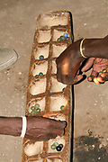 Datooga men play Mancala. Photographed in Tanzania. Mancala is one of the oldest known games to still be widely played today. Mancala is a generic name for a family of two-player turn-based strategy board games