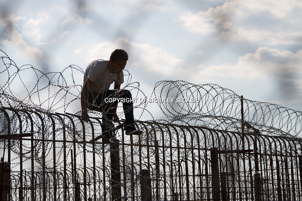 A migrant from Afghanistan attempts to scale the fence surrounding the international port in the Greek city of Patras. The port has regular ferries to Italy and Albania.