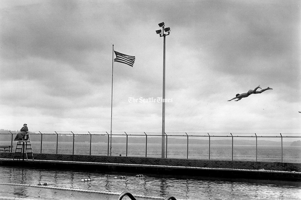 Plunging headlong into summer, regardless of the lack of sunshine, a boy finds the Laurence Colman Pool a great place to practice his dives. The pool is filled with Puget Sound water, specially captured and filtered. (Betty Udesen / The Seattle Times, 1987)