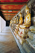 The row of Buddhas in Wat Suthat Buddhist temple, Bangkok Thailand <br />