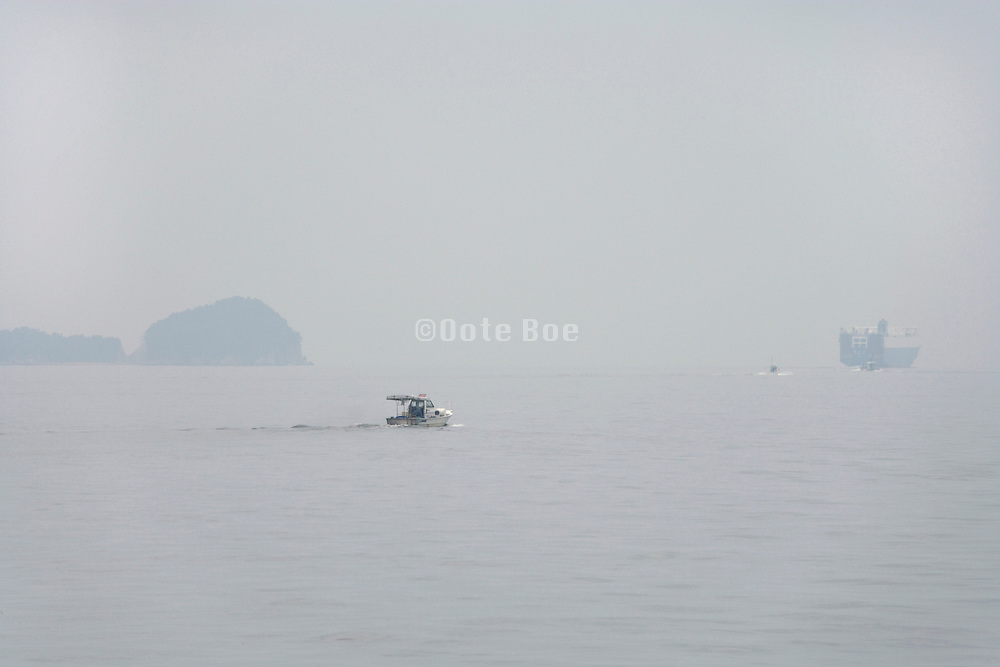 recreation boat with big commercial ship farther in the distance