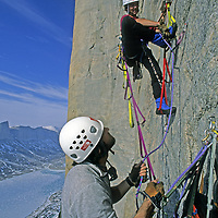 BAFFIN ISLAND, Nunavut, Canada. Mark Synnott belays as Alex Lowe leads extreme aid climbing high on Great Sail Peak, an Arctic, big wall rock climb above frozen lake in Stewart Valley. (MR)