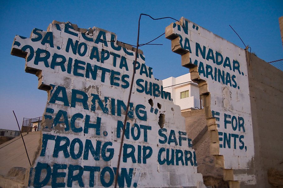 A broken sea wall frames a modern house built behind heavy concrete reinforcements on the beach at El Faro near Ensenada, Baja California Norte, Mexico.