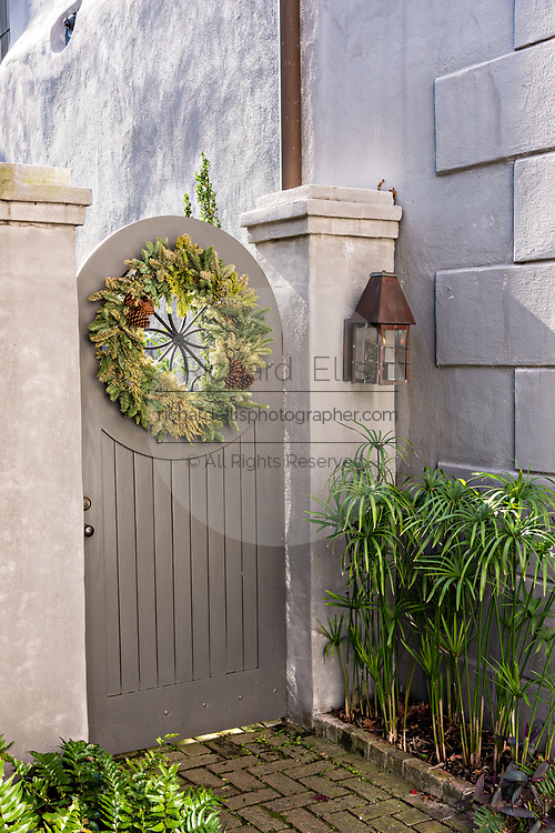 A wooden gate with a Christmas wreath at a historic home on Tradd Street in Charleston, SC.