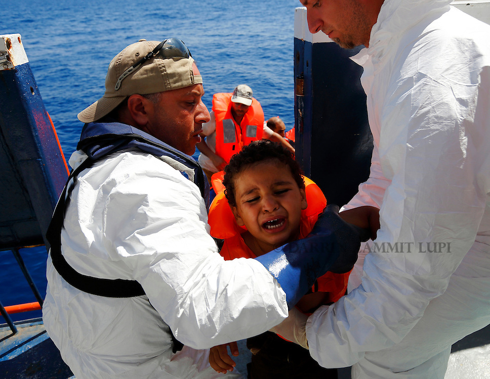 A migrant child is brought onto the Migrant Offshore Aid Station (MOAS) ship MV Phoenix after being rescued from an overloaded wooden boat off the coast of Libya August 6, 2015.  An estimated 600 migrants on the boat were rescued by the international non-governmental organisations Medecins san Frontiere (MSF) and MOAS without loss of life on Thursday afternoon, a day after more than 200 migrants are feared to have drowned in the latest Mediterranean boat tragedy after rescuers saved over 370 people from a capsized boat thought to be carrying 600.<br /> REUTERS/Darrin Zammit Lupi <br /> MALTA OUT. NO COMMERCIAL OR EDITORIAL SALES IN MALTA