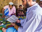 06 NOVEMBER 2014 - SITTWE, RAKHINE, MYANMAR: Rohingya Muslim men study the Koran in a hut in an IDP camp for Rohingya Muslims near Sittwe. After sectarian violence devastated Rohingya communities and left hundreds of Rohingya dead in 2012, the government of Myanmar forced more than 140,000 Rohingya Muslims who used to live in and around Sittwe, Myanmar, into squalid Internal Displaced Persons camps. The government says the Rohingya are not Burmese citizens, that they are illegal immigrants from Bangladesh. The Bangladesh government says the Rohingya are Burmese and the Rohingya insist that they have lived in Burma for generations. The camps are about 20 minutes from Sittwe but the Rohingya who live in the camps are not allowed to leave without government permission. They are not allowed to work outside the camps, they are not allowed to go to Sittwe to use the hospital, go to school or do business. The camps have no electricity. Water is delivered through community wells. There are small schools funded by NOGs in the camps and a few private clinics but medical care is costly and not reliable.   PHOTO BY JACK KURTZ