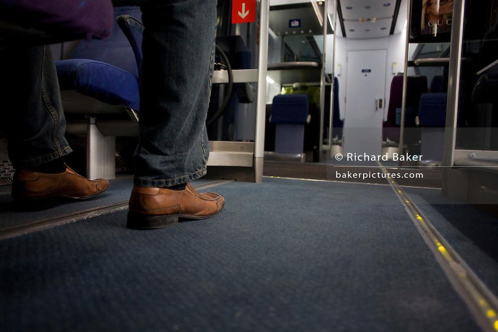 A passenger's leg is seen on the floor of a Heathrow Express train between terminals at Heathrow Airport. .