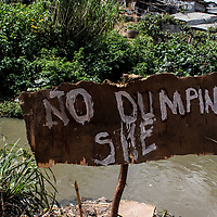 A wooden signpost designed by youth in Mathare to discourage dumping.<br /> <br /> According to Nairobi City County Solid Waste Management Act, 2015 section 36(2 and 3), any person who dumps, causes, or allows waste disposal in any premises, land or any other place not approved for such disposal is guilty of an offence and is liable of a fine not exceeding Sh200,000 or in default, to imprisonment not exceeding two years or to both.