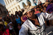 Cuban young man of African descent with a cigar in his mouth dancing wearing colourful costume. Performance in Havana old town, local dance and theatre group enacting the slave trade, colonial rule and how African religion and beliefs continuing, becoming what is now Santeria.