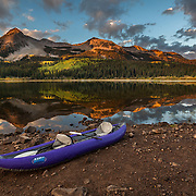 A kayak beckons on the shore of Lost Lake Slough at sunrise in the Gunnison National Forest near Kebler Pass, Colorado.