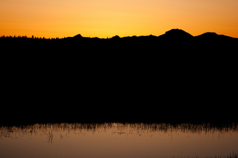 The sun setting behind Mt. Lassen from mountain meadows, Westwood, California.