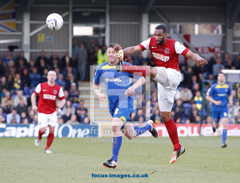 Picture by Andrew Tobin/Focus Images Ltd +44 7710 761829.27/04/2013. Nathan Pond of Fleetwood Town (red) clears from Gary Alexander of AFC Wimbledon during the npower League 2 match at the Cherry Red Records Stadium, Kingston.
