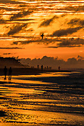People walk along the beach at sunrise on a cloudy morning June 5, 2017 in Folly Beach, South Carolina. Folly Beach is a quirky beach community outside Charleston known to locals as the Edge of America.
