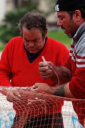 Pescatori intenti a ricucire le reti da pesca.