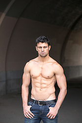 shirtless muscular man in an urban setting