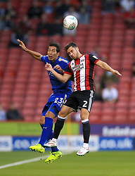 Leicester City's Leonardo Ulloa (left) and Sheffield United's George Baldock battle for the ball in the air during the Carabao Cup, Second Round match at Bramall Lane, Sheffield.