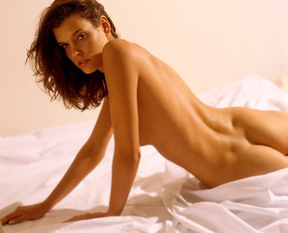 Rear view of nude woman in bed looking back toward camera