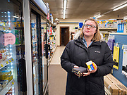 """25 FEBRUARY 2020 - BUTTERFIELD, MINNESOTA: KATIE HENDERSON, from St. James, MN., usually shops in Mankato, about 60 miles away. She works in the Butterfield Post Office and came into the True Value to get some butter. Butterfield, MN, a farming community of about 500 people 130 miles southwest of the Twin Cities. The town has been a """"food desert"""" for 10 years after its only grocery store closed in 2010. Barb Mathistad Warner and Mark Warner purchased the True Value store in Butterfield in December, 2018 and started selling groceries in the store in May, 2019. For residents of Butterfield going to a grocery store meant driving 10 miles to St. James, MN, or 20 miles to Windom, MN, the two nearest communities with grocery stores. The USDA defines rural food deserts as having at least 500 people in a census tract living 10 miles from a large grocery store or supermarket. There is a convenience store in Butterfield, but it sells mostly heavily processed, unhealthy snack foods that are high in fat, sugar, and salt.    PHOTO BY JACK KURTZ"""