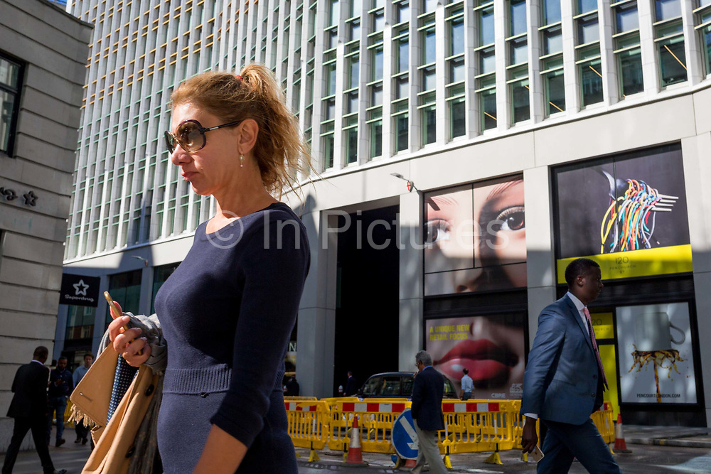 A pair of eyes and a lady passer-by on Fenchurch Street - in the heart of the capitals financial district aka The Square Mile, on 24th September 2018, in London, England.