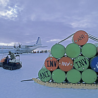 A worker at Adventure Network's Patriot Hills Expedition base ferries empty fuel drums to a C-130 Hercules that has landed on a bare ice runway.