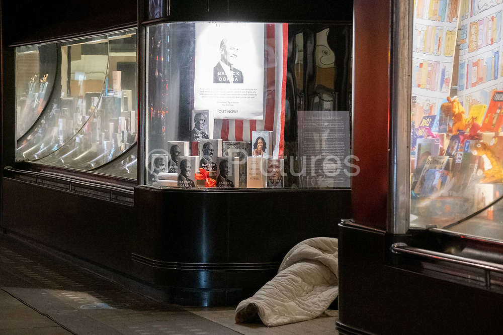 Wrapped in a sleeping bag, a homeless person lies in the doorway of Waterstones bookshop which is displaying copies of both Michelle and Barack Obamas bestselling books Becoming and A Promised Land respectively, on Piccadilly, on 2nd February 2021, in London, England.