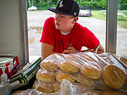 """26 JUNE 2020 - DES MOINES, IOWA: HUNTER (first name only) waits for a customer's order at Fair Food Friday in Des Moines. The 2020 Iowa State Fair, like many state fairs in the Midwest, has been cancelled this year because of the COVID-19 (Coronavirus) pandemic. The cancellation of the fair left many small vendors stranded with no income. Some of the fair food vendors in Iowa started """"Fair Food Fridays"""" on a property a few miles south of the State Fairgrounds. People drive up and don't leave their cars while vendors bring them the usual midway fare; corndogs, fried tenderloin sandwiches, turkey legs, deep fried Oreos, lemonaide and smoothies. Fair Food Friday has been very successful. The vendors serve 450-500 people per Friday and during the lunch rush people wait in line in their cars 30 - 45 minutes to place an order.     PHOTO BY JACK KURTZ"""