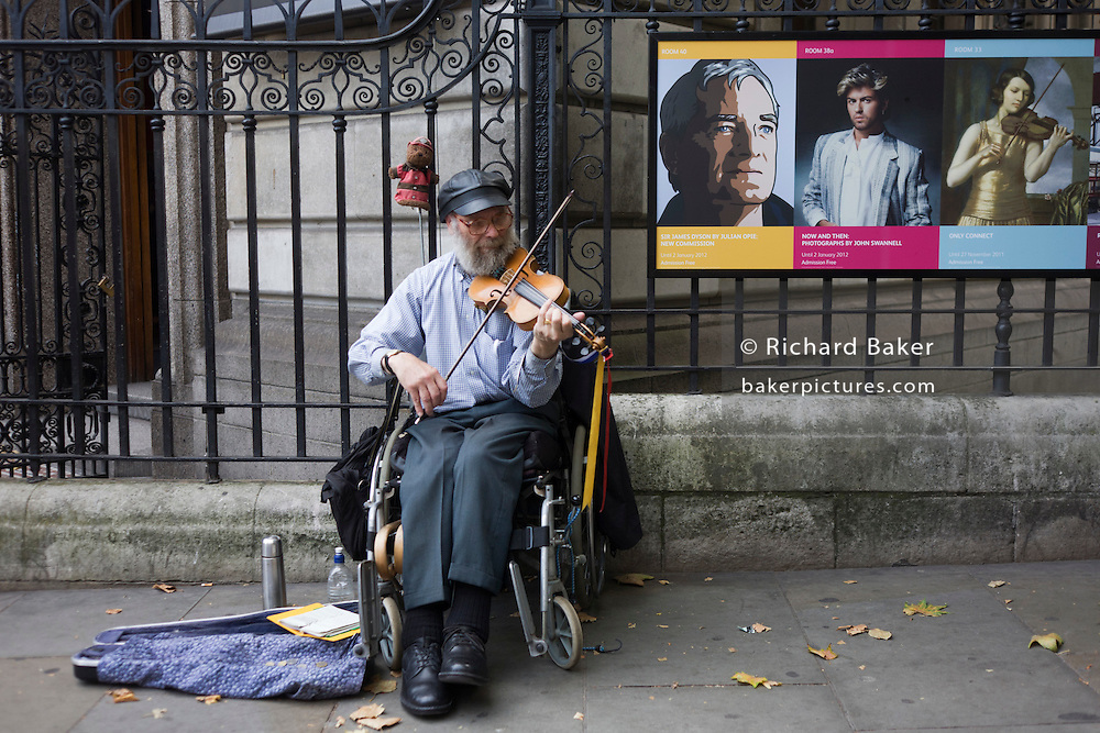 An elderly gent confined to a wheelchair plays melodies in his violin outside the National Portrait Gallery, near music poster