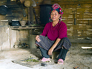 Portrait of an Oma woman preparing vegetables in her kitchen wearing her traditional headdress, Ban Nam Leng, Phongsaly province, Lao PDR. One of the most ethnically diverse countries in Southeast Asia, Laos has 49 officially recognised ethnic groups although there are many more self-identified and sub groups. These groups are distinguished by their own customs, beliefs and rituals. Details down to the embroidery on a shirt, the colour of the trim and the type of skirt all help signify the wearer's ethnic and clan affiliations.