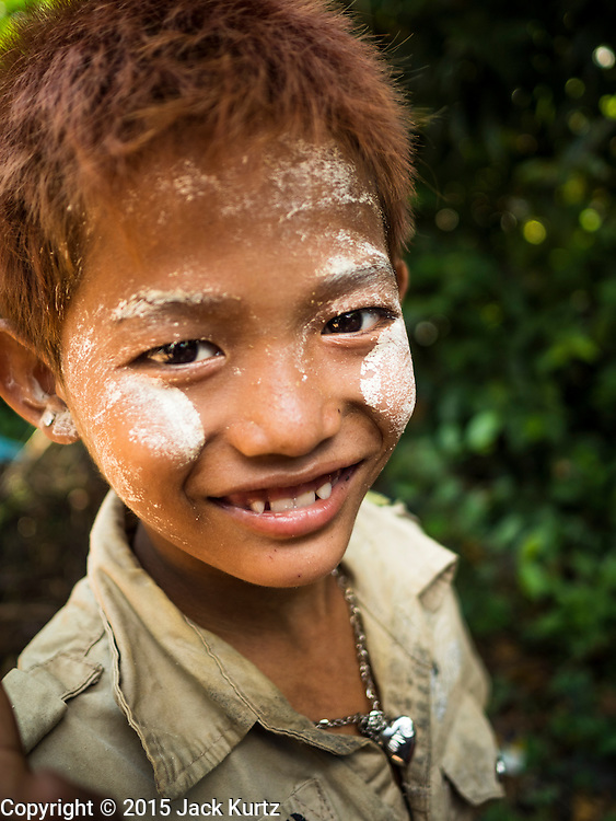 "30 OCTOBER 2015 - TWANTE, MYANMAR: A child with Burmese ""thanaka powder"" on his face in the potters' village in Twante, (also spelled Twantay) Myanmar. Twante, about 20 miles from Yangon, is best known for its traditional pottery. The pottery makers are struggling to keep workers in their sheds though. As Myanmar opens up to outside investments and its economy expands, young people are moving to Yangon to take jobs in the better paying tourist industry or in the factories that are springing up around Yangon.     PHOTO BY JACK KURTZ"