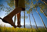 A young man walks a slackline in Grand Teton National Park, Jackson Hole, Wyoming.