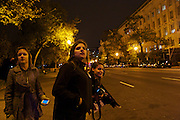 George Washington University students Shanna Helf, from left, Hannah Flom, and Laura Longman, all 18, look down 15th Street NW in Washington, D.C. to catch a glimpse of President Barack Obama's motorcade as he returned to Washington from Chicago on Wednesday evening. Each of the students voted for the first time in this year's eleciton.