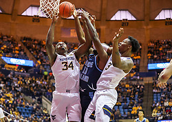 Dec 1, 2019; Morgantown, WV, USA; West Virginia Mountaineers forward Oscar Tshiebwe (34) and Rhode Island Rams forward Cyril Langevine (10) and West Virginia Mountaineers forward Gabe Osabuohien (3) jump for a rebound during the first half at WVU Coliseum. Mandatory Credit: Ben Queen-USA TODAY Sports