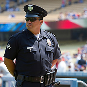 An officer with the Los Angeles Police Department keeps an eye on crowds entering and leaving Dodger Stadium in game against the National League Philadelphia Phillies.