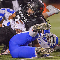 Crownpoint Eagle Darrell Etsitty (33) tumbles over McCurdy Bobcat Ace Gabrentina (50) Friday at Crownpoint High School.