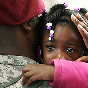 """Brianna Hudson (5) cries as she hugs her father Sergeant Amos Hudson, a member of the 82nd Combat Aviation Brigade, 82nd Airborne Division, returning to Fort Bragg after a year-long deployment in Afghanistan on. The unit provided full-spectrum aviation operations in southern Afghanistan and played a key role under heavy fire in the major assault on Marjah last month. ltqmb """"Welcome Back Dad"""""""