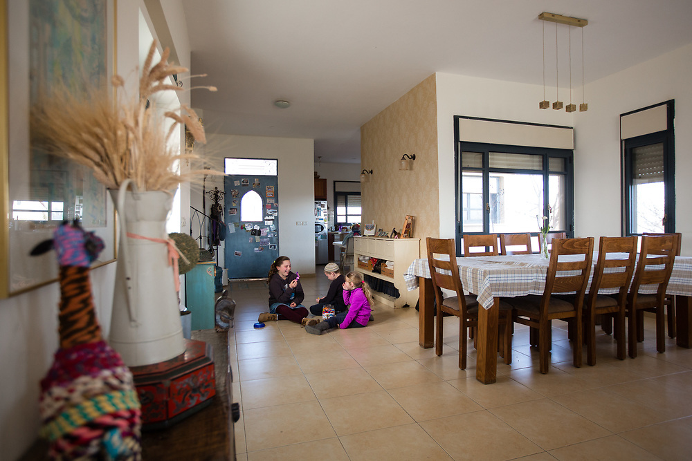 Left to right, Nili, Eitan and Yael, the children of Eliana Passentin (not pictured), owner of 'Warm Home with a Breathtaking View' bed and breakfast, which is advertised on Airbnb international home-sharing site and rental listings service, are seen playing near the dining table of the property in the West Bank Jewish settlement of Eli, on January 28, 2016.