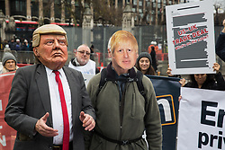 London, UK. 25 November, 2019. Activists wearing Donald Trump and Boris Johnson attend a protest by campaigners from Keep Our NHS Public, Health Campaigns Together, We Own It and Global Justice Now in Parliament Square to call on Prime Minister Boris Johnson to end privatisation of healthcare in the National Health Service (NHS).