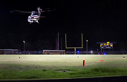 August 18, 2018 - Wellington, Florida, U.S. - Trauma Hawk lands on the field at Palm Beach Central High School to transport a shooting victim. Two adults were shot Friday night at a football game between Palm Beach Central and William T. Dwyer high schools, authorities said. The gunfire sent players and fans screaming and stampeding in panic during the fourth quarter of the game at Palm Beach Central High School in Wellington, Florida on August 17, 2018. (Credit Image: © Allen Eyestone/The Palm Beach Post via ZUMA Wire)
