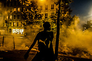 Paris, France, 03/06/20 | A young woman is feeling from teargas fired by French riot police during clashses in the midst of a Black Lives Matter protest.