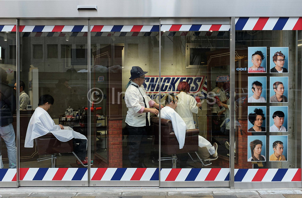 Barber shop in Omotosando with window display of quirky hairstyles. Omotosando is known as one of the foremost :architectural showcases in the world featuring a multitude of high fashion flagship stores. Tokyo, Japan.