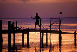 Fishing off a pier at sunset.