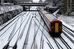 © Licensed to London News Pictures. 21/01/2013, London, UK. A train runs on snow covered tracks in Croydon, South London, Monday, Jan. 21, 2013. Britain is continue affect by cold weather and snow. Photo credit : Sang Tan/LNP