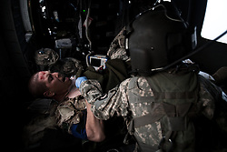 """A Canadian soldier who has just lost his left foot to an IED strike  in western Kandahar province screams out in pain as a flight medic and medical officer work to treated and stabilize him. Scenes from the medical evacuations of wounded Americans, Canadians, and Afghan civilians and soldiers being flown by Charlie Co. 6th Battalion 101st Aviation Regiment of the 101st Airborne Division. Charlie Co. - which flies under the call-sign """"Shadow Dustoff"""" - flies into rush the wounded to medical care out of bases scattered across Oruzgan, Kandahar, and Helmand Provinces in the Afghan south. These images were taken of missions flown out of Kandahar Airfield in Kandahar Province and Camp Dwyer in Helmand Province."""