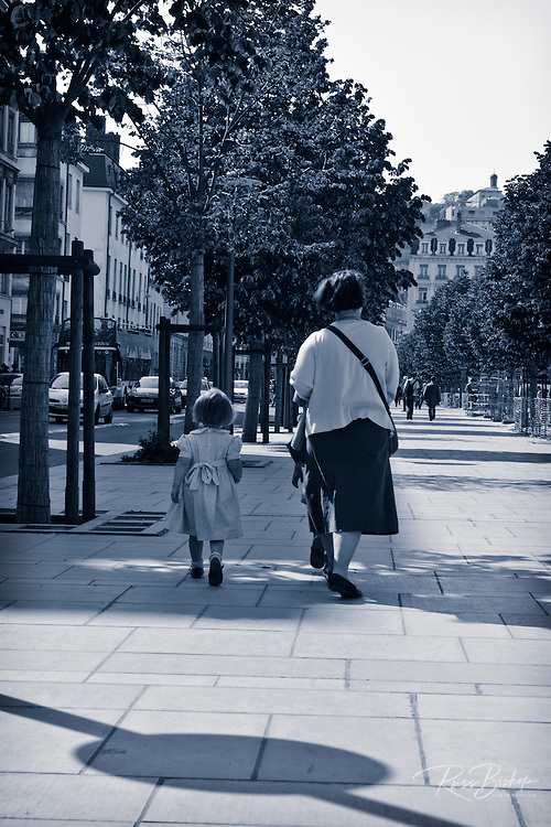Mother and daughter walking on sidewalk, Lyon, France (UNESCO World Heritage Site)