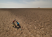 A team of geologists are getting core samples of earth in a dry lake. Zang-e Ahmad, place name. Shurgaz Hamun.