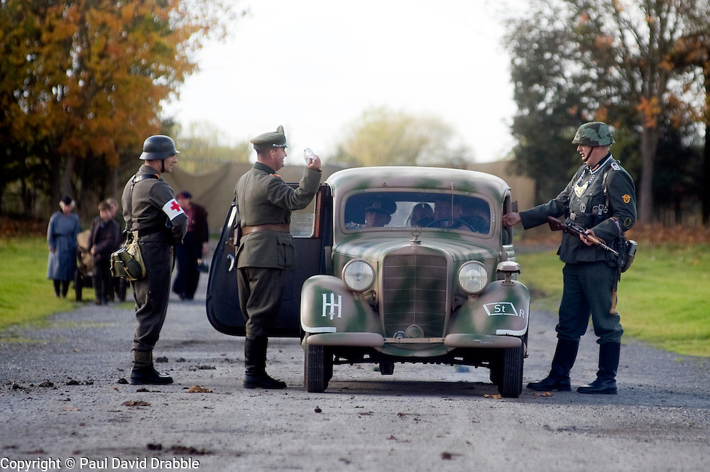 Pickering 1940s war weekend Northern World war Two Association battle reenactment. Three members of the German Feldgendarmerie or field police living history group stop an officers Mercedes at a check point.. October 2009 Image Copyright Paul David Drabble