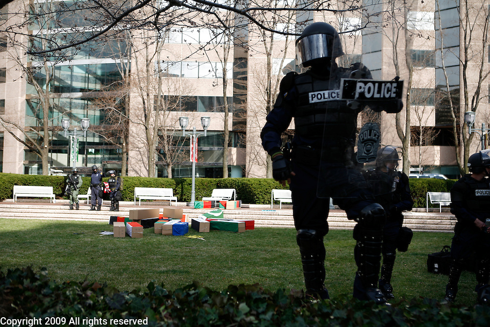 """Police in full riot gear guard General Dynamics during a march on the pentagon and against the war in Iraq. The protesters delivered fake coffins to several companies they allege have """"war profiteered"""" in Iraq and Afghanistan. March 21, 2009. Washington, D.C."""