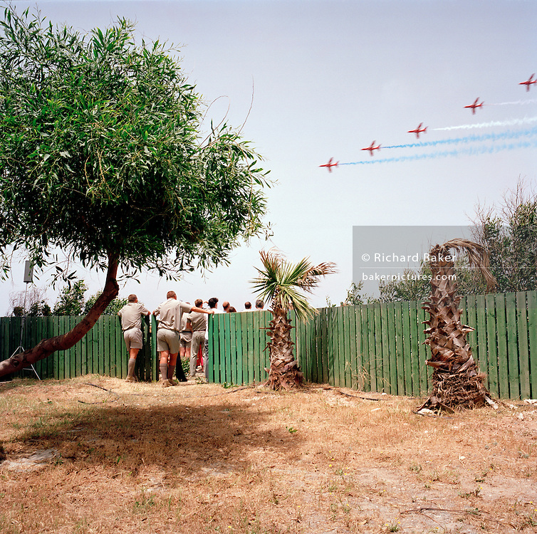 Spectators at the The Princess Margaret Hospital (TPMH) on the Akrotiri peninsula, about 4 kilometres from the RAF Station at Akrotiri, admire the elite 'Red Arrows', Britain's prestigious Royal Air Force aerobatic team, as they perform one of their first public shows of the year. RAF staff and patients are allowed on to the grass outside the hospital building for this free show, given in honour of local charity fund-raisers of the Cyprus-based RAF Association whose guests form one of the smallest crowds to watch a Red Arrows display. Here, the team perform The Twizzle manoeuvre in front of the small crowd who stand by a green fence, matching tree and palm tree stumps. The bare earth is baked hard by the lack of rain and it almost looks like a desert scene as five of the nine jets speed overhead,