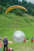 India, Vashisht near Manali, Kullu District, Himachal Pradesh, Northern India local tourists enjoying a day of sport and recreation on the mountain side with gliders and rolling balls